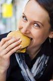 κατανάλωση της νόστιμης γυναίκας χάμπουργκερ Στοκ Φωτογραφία