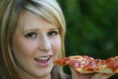 κατανάλωση της φέτας πιτσών κοριτσιών στοκ εικόνα με δικαίωμα ελεύθερης χρήσης