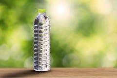 Κατανάλωση του μπουκαλιού νερό με τη μαλακή σκιά ξύλινο tabletop στο θολωμένο πράσινο υπόβαθρο bokeh με το μαλακό φως του ήλιου Στοκ Εικόνες