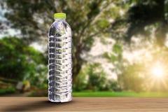 Κατανάλωση του μπουκαλιού νερό με τη μαλακή σκιά ξύλινο tabletop στο θολωμένο πάρκο με το μαλακό υπόβαθρο φωτός του ήλιου Στοκ Εικόνες