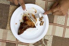 Κατανάλωση του πασσάλου από το πιάτο με τα χέρια ατόμων δικράνων και μαχαιριών Στοκ Φωτογραφίες