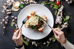 Κατανάλωση του πιάτου εστιατορίων στο άσπρο πιάτο στο μαύρο υπόβαθρο Στοκ φωτογραφία με δικαίωμα ελεύθερης χρήσης
