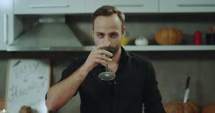 Κατανάλωση του πράσινου κοκτέιλ στο νεαρό άνδρα κομμάτων αποκριών σε μια μαύρη μπλούζα που κοιτάζει στη κάμερα απόθεμα βίντεο