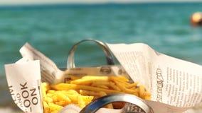 Κατανάλωση των νόστιμων τραγανών τηγανιτών πατατών στην παραλία απόθεμα βίντεο