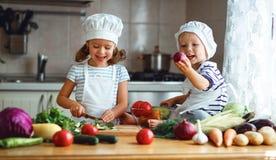 κατανάλωση υγιής Τα ευτυχή παιδιά προετοιμάζουν τη φυτική σαλάτα στο kitc Στοκ Φωτογραφία