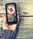 κατανάλωση υγιής Smartphone σε ένα θηλυκό χέρι εικόνα επίδειξης της φράουλας milkshake Στοκ εικόνα με δικαίωμα ελεύθερης χρήσης