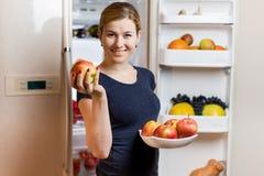 κατανάλωση έννοιας υγιής Ευτυχής γυναίκα με το μήλο που στέκεται στο ανοιγμένο ψυγείο με τα φρούτα, τα λαχανικά και τα υγιή τρόφι Στοκ εικόνα με δικαίωμα ελεύθερης χρήσης