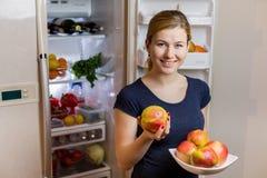 κατανάλωση έννοιας υγιής Ευτυχής γυναίκα με το μήλο που στέκεται στο ανοιγμένο ψυγείο με τα φρούτα, τα λαχανικά και τα υγιή τρόφι Στοκ Φωτογραφία