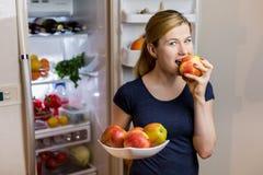 κατανάλωση έννοιας υγιής Ευτυχής γυναίκα με το μήλο που στέκεται στο ανοιγμένο ψυγείο με τα φρούτα, τα λαχανικά και τα υγιή τρόφι Στοκ φωτογραφία με δικαίωμα ελεύθερης χρήσης