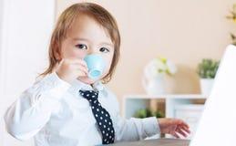 Κατανάλωση κοριτσιών μικρών παιδιών από μια κούπα μπροστά από ένα lap-top Στοκ φωτογραφίες με δικαίωμα ελεύθερης χρήσης