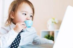 Κατανάλωση κοριτσιών μικρών παιδιών από μια κούπα μπροστά από ένα lap-top Στοκ Φωτογραφίες
