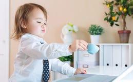 Κατανάλωση κοριτσιών μικρών παιδιών από μια κούπα μπροστά από ένα lap-top Στοκ εικόνα με δικαίωμα ελεύθερης χρήσης