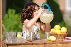 Κατανάλωση μικρών κοριτσιών από τη στάμνα λεμονάδας Στοκ φωτογραφία με δικαίωμα ελεύθερης χρήσης