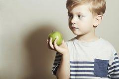κατανάλωση παιδιών μήλων Μικρό παιδί με το πράσινο μήλο μακρο λευκό στούντιο υγείας τροφίμων νιφάδων καλαμποκιού ανασκόπησης καρπ Στοκ Εικόνα