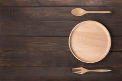 Κατανάλωση της έννοιας Ξύλινο πιάτο, ξύλινο κουτάλι και ξύλινο δίκρανο που τίθενται στο W Στοκ Φωτογραφίες