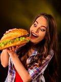 κατανάλωση της γυναίκας & Δάγκωμα κοριτσιών πολύ μεγάλο burger Στοκ εικόνες με δικαίωμα ελεύθερης χρήσης
