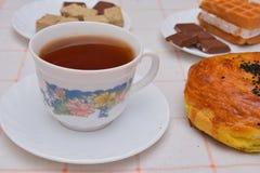 Κατανάλωση τσαγιού βραδιού με τις γκοφρέτες, σοκολάτα και halvah Στοκ Φωτογραφίες