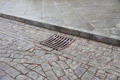 Καταπακτή υπονόμων αποξηράνσεων στη φθινοπωρινή πόλη που καλύπτεται Σχάρα του τρόπου αγωγών λυμάτων waterspout στην οδική επιφάνε Στοκ φωτογραφίες με δικαίωμα ελεύθερης χρήσης