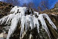 Καταπληκτικά παγάκια που κρεμούν από έναν σχηματισμό βράχου στα βουνά κατά τη διάρκεια του κρύου χειμώνα Στοκ εικόνα με δικαίωμα ελεύθερης χρήσης