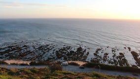 Καταπληκτική άποψη της θάλασσας κατά τη διάρκεια του ηλιοβασιλέματος, που βλέπει από μια καλή και αγροτική άποψη σε Cabo Mondego, φιλμ μικρού μήκους