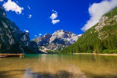 Καταπληκτική άποψη της λίμνης braies με τις ξύλινες βάρκες στο νερό, που περιβάλλεται από τα βουνά δολομιτών Alto Trentino adige στοκ φωτογραφία με δικαίωμα ελεύθερης χρήσης