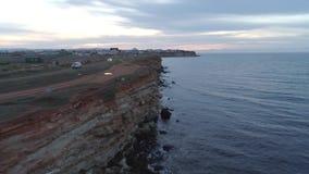 Καταπληκτική άποψη του απότομου απότομου βράχου μπροστά από τη θάλασσα κοντά στο δρόμο επαρχίας με την κίνηση των αυτοκινήτων και απόθεμα βίντεο