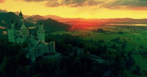 Καταπληκτική εναέρια άποψη ηλιοβασιλέματος του κάστρου Neuschwanstein, χρυσός ουρανός, λυκόφως σχετικά με τις βαυαρικές Άλπεις, Β φιλμ μικρού μήκους