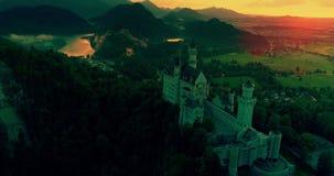 Καταπληκτική εναέρια άποψη ηλιοβασιλέματος του κάστρου Neuschwanstein, χρυσός ουρανός, λυκόφως σχετικά με τις βαυαρικές Άλπεις, Β απόθεμα βίντεο