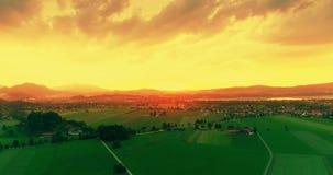 Καταπληκτική εναέρια άποψη ηλιοβασιλέματος των πράσινων ευρωπαϊκών τομέων, χρυσός ουρανός, λυκόφως σχετικά με τις βαυαρικές Άλπει φιλμ μικρού μήκους