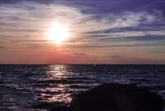 Καταπληκτική ηλιοβασίλεμα ή ανατολή στη δύσκολη θάλασσα ή την ωκεάνια ακτή με το πλέοντας σκάφος στον ορίζοντα στοκ φωτογραφία