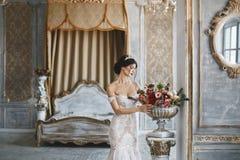 Καταπληκτική ομορφιά, με μεγάλο στήθος brunette, πρότυπο κορίτσι σε μια τοποθέτηση φορεμάτων γαμήλιων δαντελλών στο εσωτερικό Στοκ Φωτογραφία