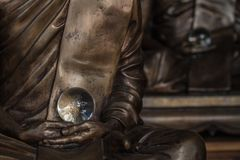 Καταπληκτική σφαίρα κρυστάλλου στα χέρια του αγάλματος μοναχών Στοκ Εικόνες