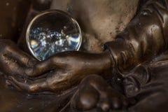 Καταπληκτική σφαίρα κρυστάλλου στα χέρια του αγάλματος μοναχών Στοκ φωτογραφία με δικαίωμα ελεύθερης χρήσης