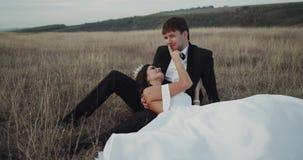Καταπληκτικοί νύφη και νεόνυμφος στη μέση του τοπίου που καθορίζουν τη νύφη σχετικά με ρομαντικό το πρόσωπό του απόθεμα βίντεο