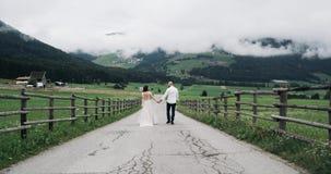 Καταπληκτικός εκλεκτής ποιότητας δρόμος με τη φανταστική άποψη των βουνών και με το ελκυστικό ζεύγος που περπατά κάτω κίνηση αργή φιλμ μικρού μήκους