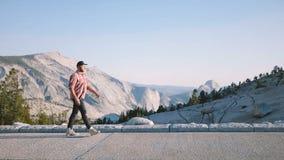 Καταπληκτικός στατικός πυροβολισμός πλάγιας όψης του νέου ευτυχούς ατόμου που περπατά κατά μήκος της επικής θέας βουνού στο εθνικ απόθεμα βίντεο
