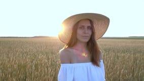 Καταπληκτικό πορτρέτο της όμορφης γυναίκας που στέκεται στον τομέα του ώριμου χρυσού σίτου φιλμ μικρού μήκους