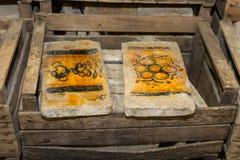 Καταπονημένα χρωματισμένα τούβλα στο καφετί ξύλινο κιβώτιο Στοκ Φωτογραφίες