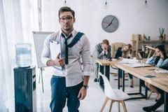 καταπονημένος ακατάστατος επιχειρηματίας με την περιοχή αποκομμάτων που στέκεται στο γραφείο καθμένος συναδέλφων Στοκ Φωτογραφίες