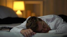 Καταπονημένος επιχειρηματίας πεσμένος κοιμισμένος στο κρεβάτι κοντά στα έγγραφα και το lap-top, έγκαυμα έξω φιλμ μικρού μήκους