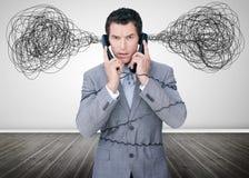 Καταπονημένος επιχειρηματίας που κρατά δύο τηλέφωνα στοκ εικόνα