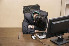Καταπονημένος, κουρασμένος νέος ύπνος επιχειρηματιών στην αρχή στοκ φωτογραφία