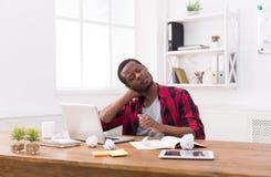 Καταπονημένος μαύρος επιχειρηματίας στο περιστασιακό γραφείο, εργασία με το lap-top Στοκ φωτογραφία με δικαίωμα ελεύθερης χρήσης