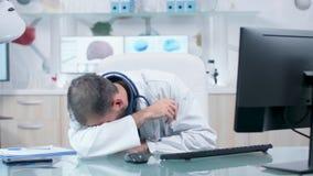 Καταπονημένος sicentist ή γιατρός στο σύγχρονο γραφείο του απόθεμα βίντεο