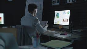 Καταπονημένο επιχειρησιακό άτομο που αναλύει το οικονομικά διάγραμμα και το διάγραμμα στο γραφείο νύχτας φιλμ μικρού μήκους