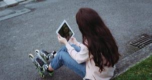 Καταπληκτική λεπτομέρεια του νέου κοριτσιού με την όμορφη συνεδρίαση τρίχας στην οδό, υπολογιστής και λήψη οθόνης αφής ταμπλετών  απόθεμα βίντεο