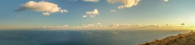 Καταπληκτική ευρεία πανοραμική θέα βουνού με το συμπαθητικό ουρανό και τη θάλασσα στο θερμό φως ήλιων το απόγευμα Στοκ εικόνες με δικαίωμα ελεύθερης χρήσης