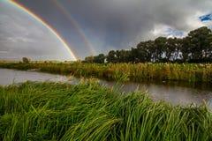 Καταπληκτικό διπλό ουράνιο τόξο πέρα από το μικρό ποταμό Στοκ Φωτογραφίες
