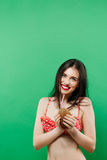 Καταπληκτικό χαμόγελο Brunette στη φωτεινή τοποθέτηση Swimwear με το κοκτέιλ στο στούντιο στο πράσινο υπόβαθρο Στοκ φωτογραφία με δικαίωμα ελεύθερης χρήσης