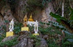 Καταπληκτικό χρυσό άγαλμα του Βούδα στην όμορφη φύση που σκαρφαλώνει από μια πλευρά απότομων βράχων Στοκ φωτογραφία με δικαίωμα ελεύθερης χρήσης